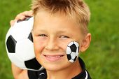 Young happy boy with painted face and soccer ball.