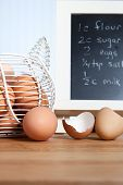 picture of chicken-wire  - Fresh brown organic eggs with a recipe in a country kitchen with a wire basket of eggs - JPG