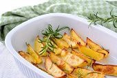 stock photo of potato-field  - Baked potato wedges with rosemary in an oven dish