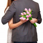 Young Couple In Love Make A Heart And Hands Are Holding A Bouquet Of Tulips. The Concept Of Valentin