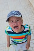 stock photo of crying boy  - Crying boy standing on the street in town - JPG