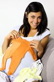 Beautiful Young Pregnant Woman Showing Baby Clothes