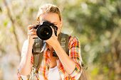 young woman taking photos in autumn forest with dslr