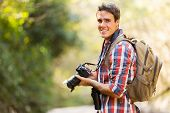 young man hiking in mountain with dslr camera