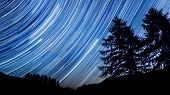 star trail. Night sky over mountain forest.