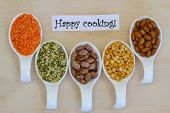 Happy cooking card with selection of pulses on porcelain spoons on wooden surface