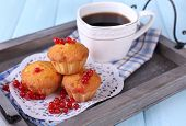 Tasty muffin with red currant berries on tray, on color wooden background