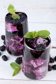 Tasty cool blackberry lemonade with ice on wooden table