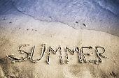 Word Summer handwritten on the sandy beach