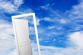 Open door on blue sunny sky with fluffy clouds. Concepts like new life, success, future perspective,