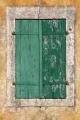 Old green textured shutters with cracks