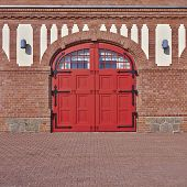 entrance with arched red door and windows