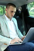 Man sitting in car with laptop