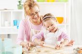 foto of granddaughter  - Beautiful happy grandmother and granddaughter a rolling pin together in the Kitchen - JPG
