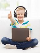home, childhood, leisure, technology and music concept - smiling little boy with tablet pc computer and headphones showing thumbs up at home