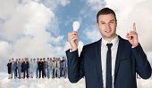 Businessman holding light bulb and pointing against blue sky with white clouds