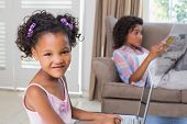 Cute daughter using laptop at desk with mother on couch at home in the living room