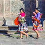 CUZCO, PERU, MAY 1, 2014 - Two girls in folk costumes walk carrying llama babies. They earn money po
