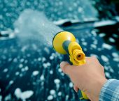 Car care - Woman using a garden spray gun