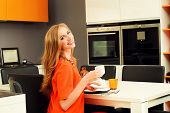 Beautiful young woman having a dinner at a kitchen at home. Home interior.