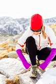 Runner Tying Sport Shoe In Mountains On Trail