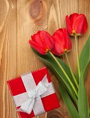 Fresh tulips and gift box over wooden table background