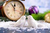 Alarm clock, decorative birds with Christmas decorations on light background