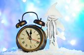 Alarm clock and Christmas decorations in snow on bright background