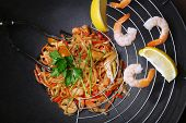 Chinese noodles with vegetables and seafood in wok