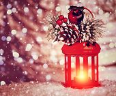Beautiful Christmas glowing lantern with stylish decor on the top on blurry snowy background, festive still life, cute wintertime decoration