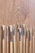 Row Of Wooden Paint Brushes On Table Background