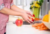 Washing fruit, woman washing red apple under the tap