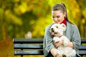 Young woman holding cute maltese dog,  outdoor in park