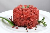 very big raw hamburger cutlet with sprouts and chilli pepper on white plate over black background