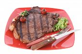 new york meat style beef steak fillet on red plate with hot chili pepper and green salad isolated over white background with stainless steel cutlery