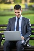 Businessman sitting on bench with laptop in park