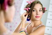 Young  girl with hair curlers in hair standing front  the mirror puts earring