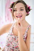 Happy teen girl applying lipstick front mirror