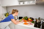 Woman in kitchen using tablet reading recipe