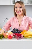 Young smiling  woman kitchen in with fruits and vegetables