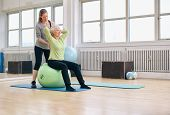 Female Trainer Helping Senior Woman Exercising In Gym
