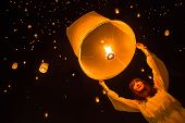 CHIANG MAI, THAILAND - NOVEMBER 8, 2014: Unidentified woman release Khom Loi, the sky lanterns during Yi Peng or Loi Krathong festival on November 8, 2014 in Mae Jo University, Chiang Mai, Thailand.