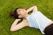 Healthy and beautiful young woman lying on grass in park