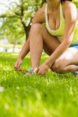 Athletic woman tying her shoelace in the park