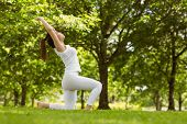 Side view of healthy and beautiful young woman doing stretching exercises at park