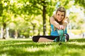 Fit blonde stretching on the grass on a sunny day