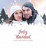 young winter couple against feliz navidad