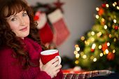 Pretty redhead holding mug of hot drink at home in the living room