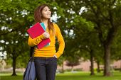 Smiling female college student with books looking away in the park