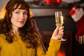 Redhead holding glass of champagne on couch at christmas at home in the living room